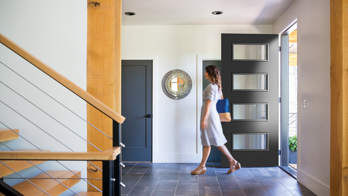 Modern style home entryway with a woman walking into the house passing a 4 lite black door