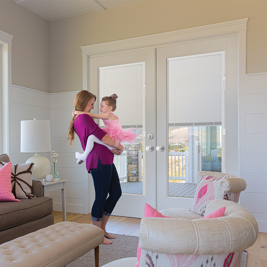 A mom holding her young daughter in a pink ballerina outfit in a living room in front of VistaGrande double doors with built in mini blinds