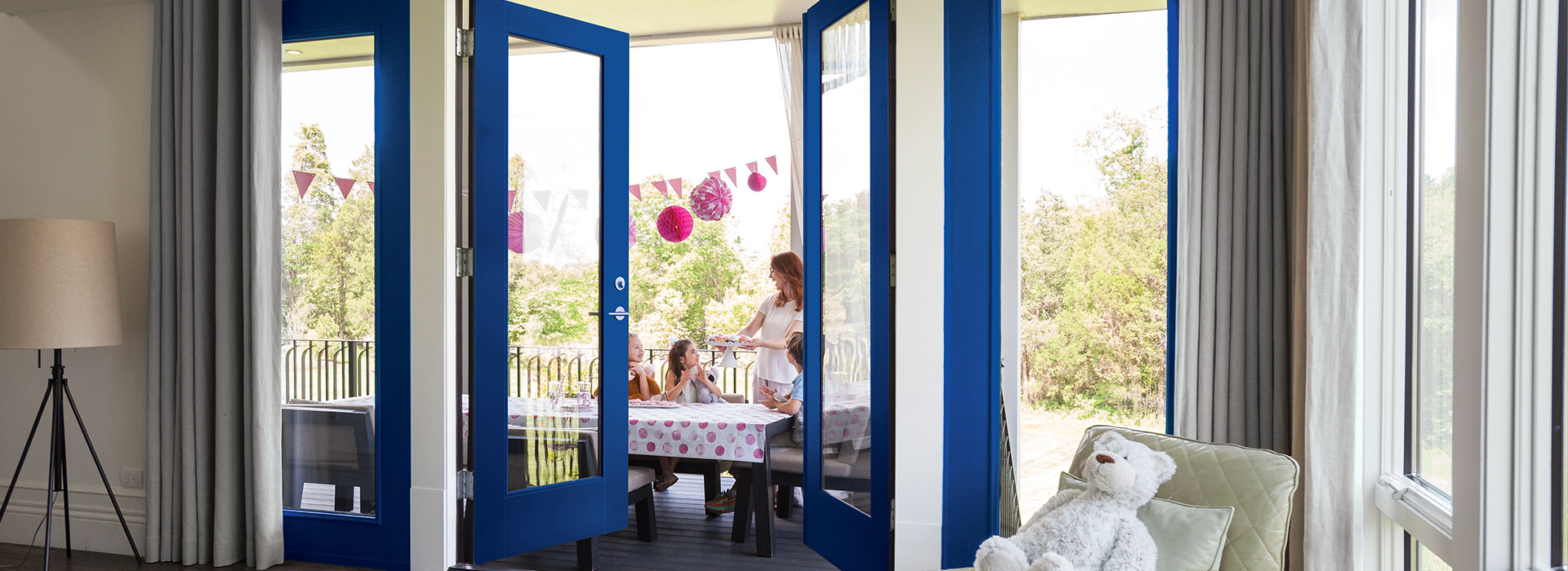 Full lite exterior blue VistaGrande double doors open view of a little girl's party with pink décor